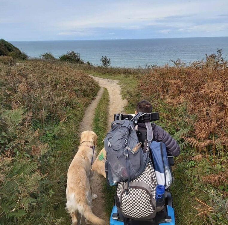 Martyn Sibley in his wheelchair holding dog Sunny on a lead walking along a path on the coast