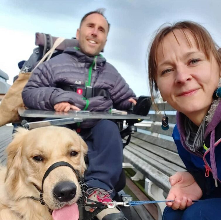 Martyn Sibley in his wheelchair outside with Kasia and dog sunny sat in front