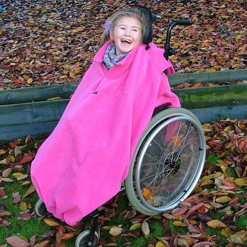 Young disabled girl in fuschia fleece wheelchair cover