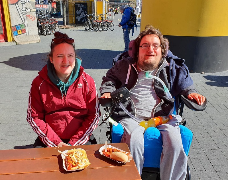 Derry Felton in his wheelchair at a cafe in Berlin having a Frankfurter