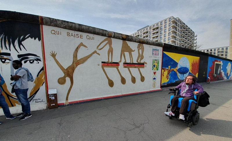 Derry Felton in his wheelchair beside the Berlin wall covered in artwork