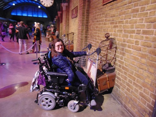 Emma in her wheelchair holding the luggage carrier going through a brick wall