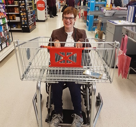 Lucy in a supermarket with a shopping basket on her wheelchair