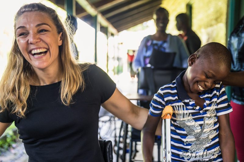 Sophie Morgan laughing with a young disabled child in Africa