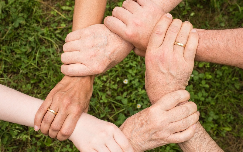 Five hands together in a circle holding each other's wrists