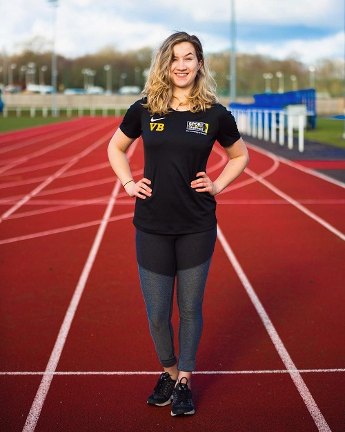 Victoria Baskett standing on a running track in a black T-shirt and leggings