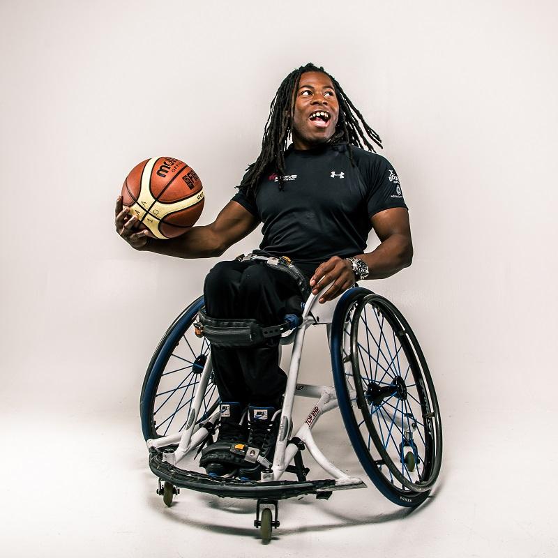 Ade Adepitan holding a basketball
