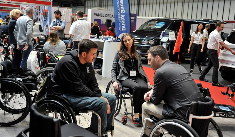 A wheelchair user talking to a manufacturer at Naidex
