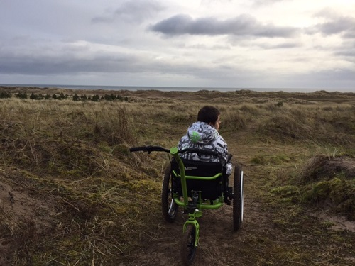 Andrew in the MT Push all-terrain wheelchair in a field with rough grasses