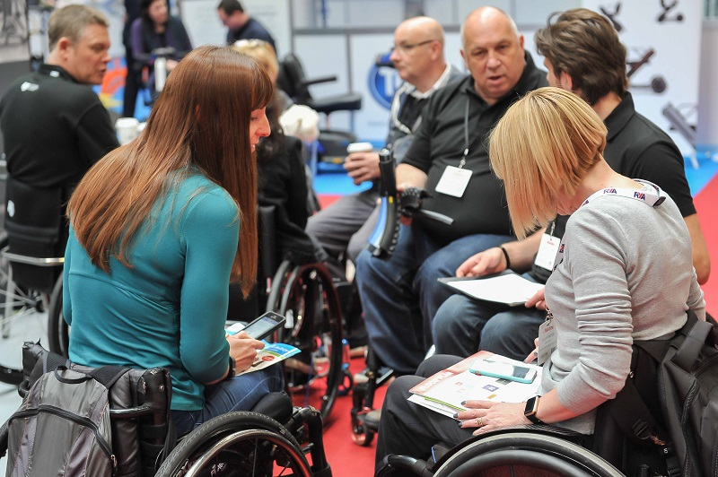 Men and women in wheelchairs talking at Naidex