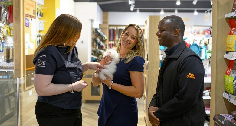 Woman at Pets Corner holding a white rabbit with two staff members either side