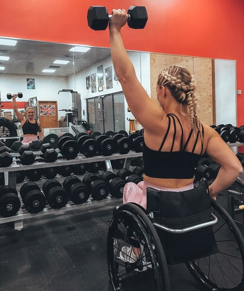 Sophie Carrigill in her wheelchair lifting a weight in front of a mirror in a gym
