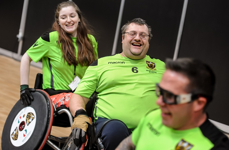 Three wheelchair users trying out a sport at Naidex
