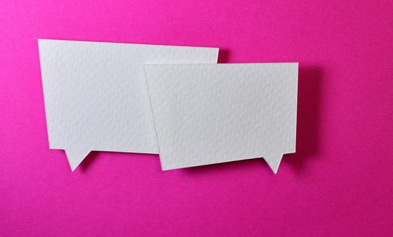 Two white speech bubbles on bright pink background