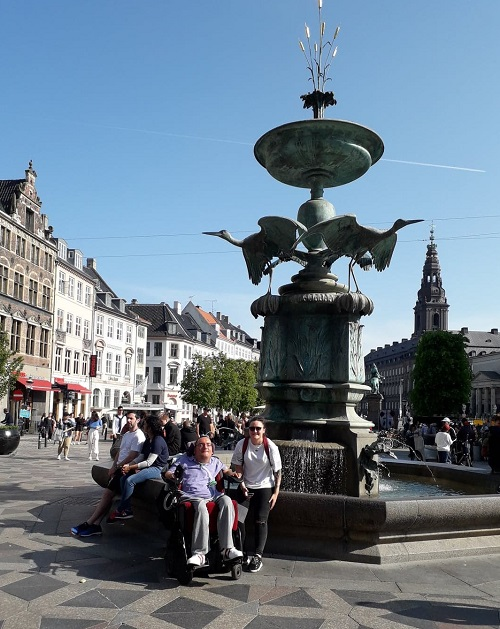 Wheelchair user Derry with his PA in front of a fountain in Copenhagen
