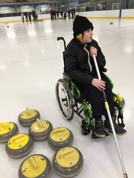 Phoenixin his manual wheelchair holding a curling brush and sat next to yellow curling stones