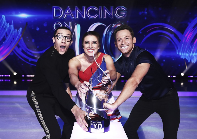 Dancing on Ice finalists Libby Clegg, Perri Kiely and Joe Swash on the ice rink holding the trophy