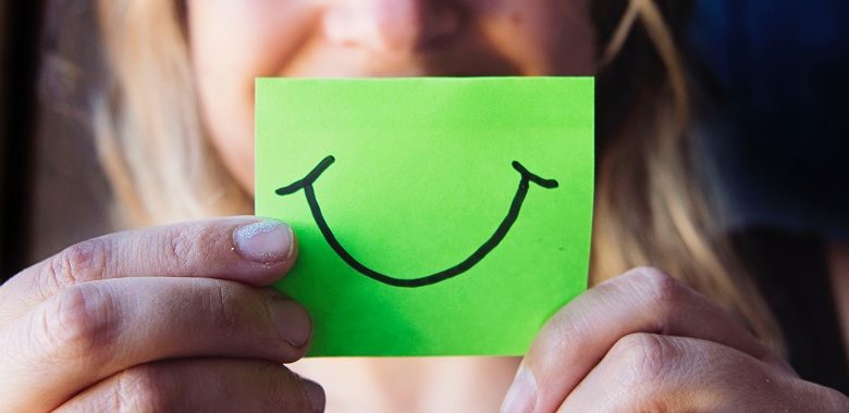 Woman holding green paper with a smile on it