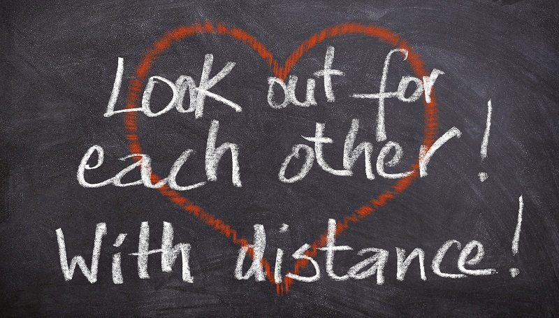 Words 'look out for each other with distance' in chalk on a blackboard