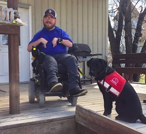 Alex in his garden with his service dog