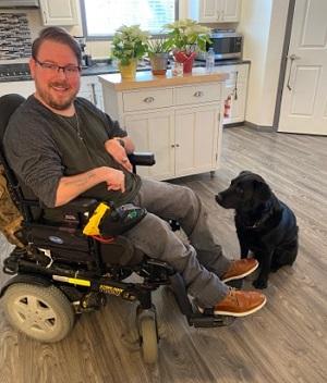 Alex in his kitchen with his black Labrador dog