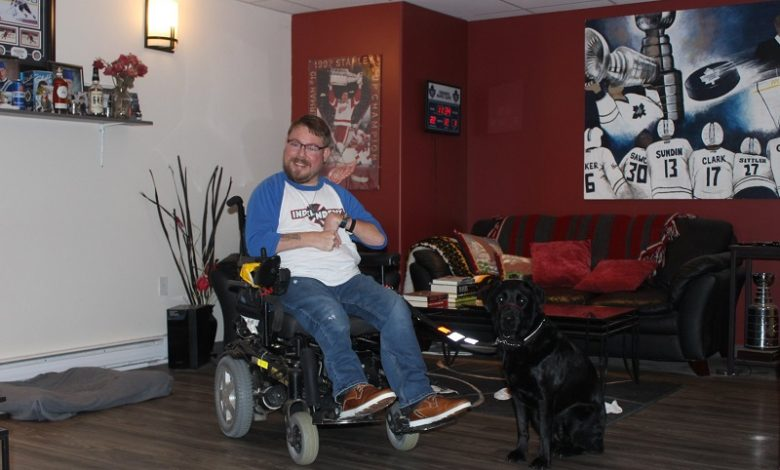 Alex in his living room with his black Labrador dog
