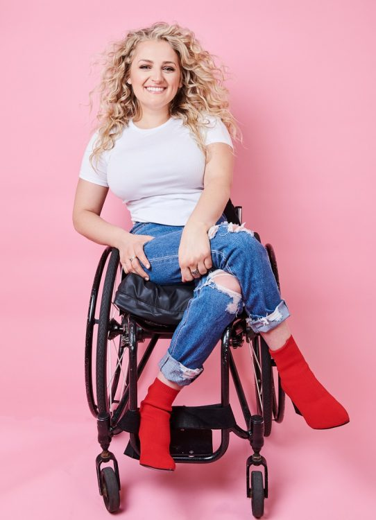 Ali Stroker in her wheelchair with a white t-shirt, jeans and red boots in front of a pink background