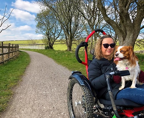 Carrie-Ann in her all-terrain wheelchair on a walk with her dog