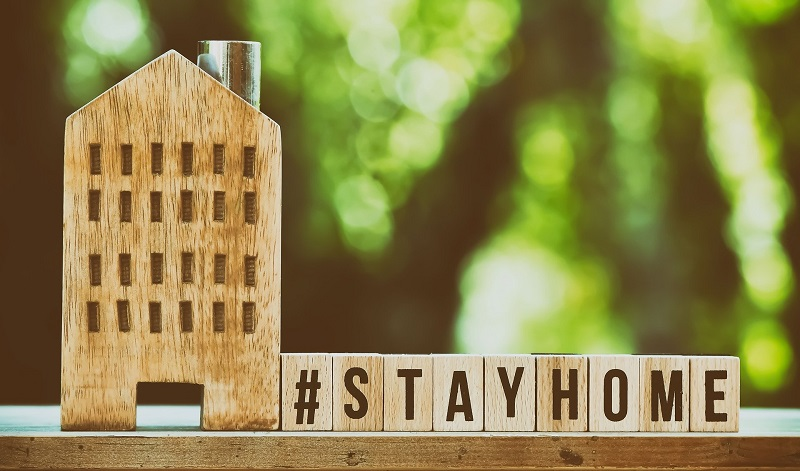 House cut out of wood and wooden blocks spelling out stay home