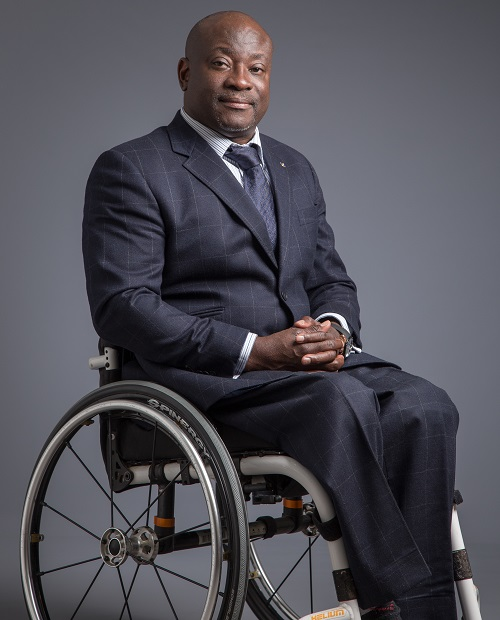 Mark Esho in a suit and his wheelchair on a grey background