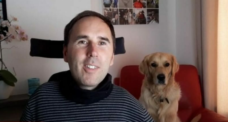 Martyn Sibley with his dog Sunny on a chair behind him