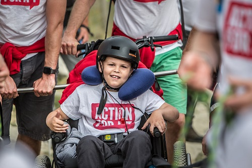 Zach smiling while climbing Mount Snowdon in a Mountain Trike all-terrain wheelchair