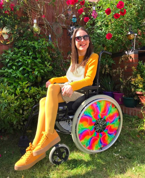 Rebecca sits in her colorful wheelchair in a garden wearing yellow.