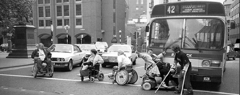Black and white image from the 60s of disaled people blocking a road
