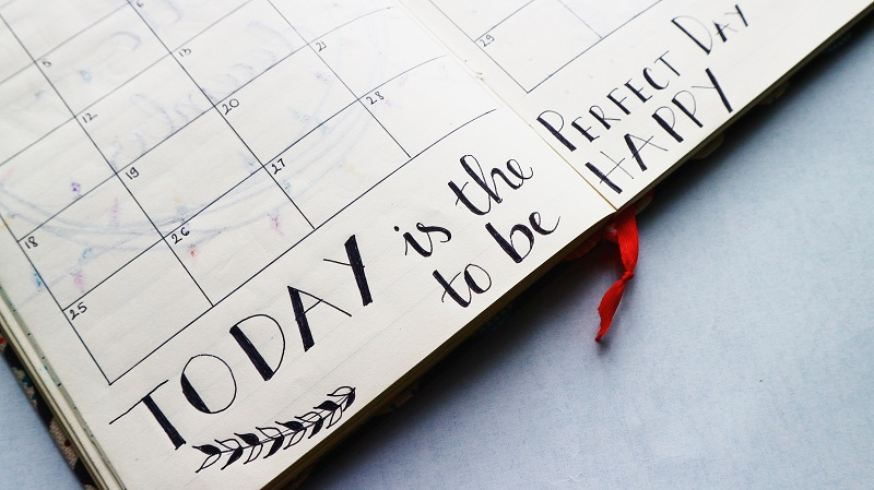 Diary with the words today is the perfect day to be happy written at the bottom