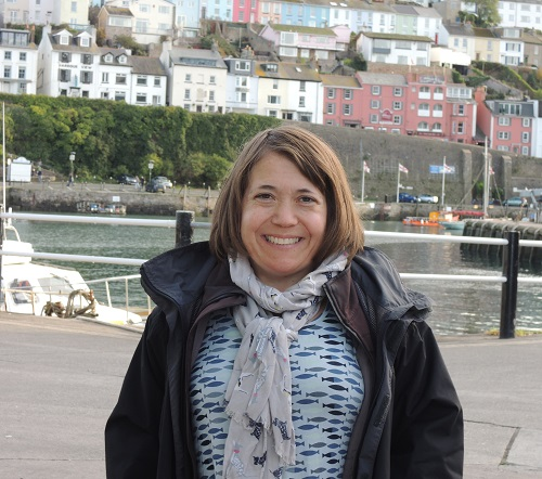 Emma West standing in front of a harbour