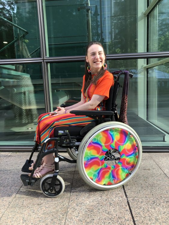 Rachel smiling and sitting her wheelchair in a bright orange outfit.