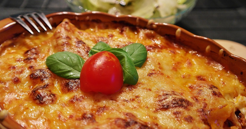 Lasagne in a round bowl with a tomato on top