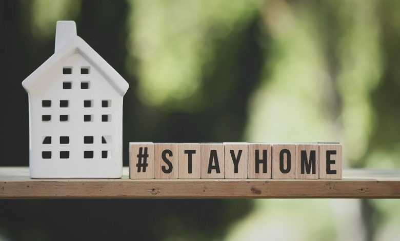 Stay home words spelt out on wooden letter blocks next to a white china house
