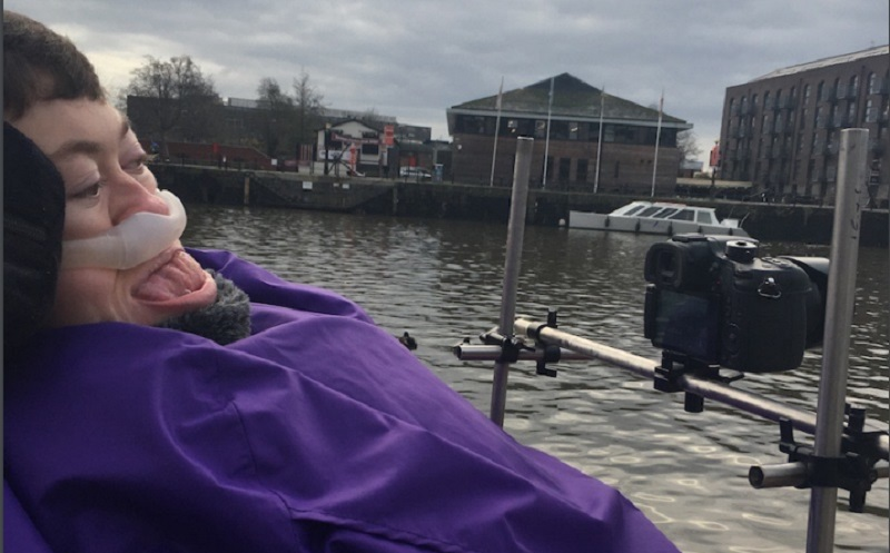 Stephanie Castelete-Tyrrell in her wheelchair behind a camera filming water in front of her
