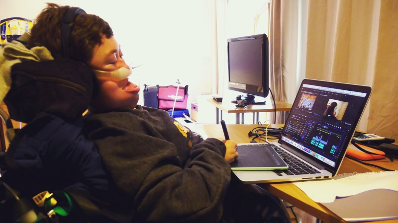Stephanie Castelete-Tyrrell in her wheelchair at her laptop on a desk editing a film