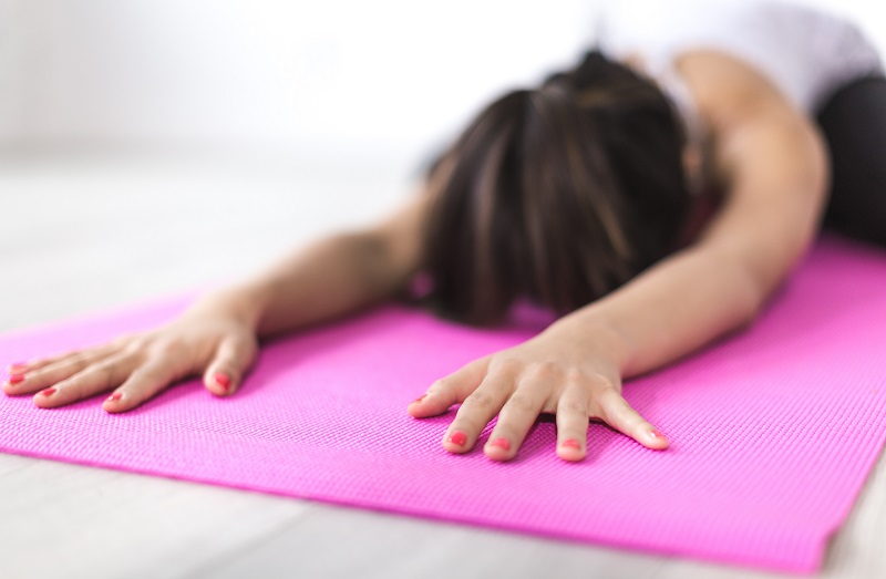 Woman laying on a pilates mat bending forward stretching