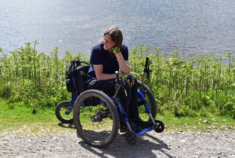 Craig Grimes in his all-terrain wheelchair on an uneven path next to a lake