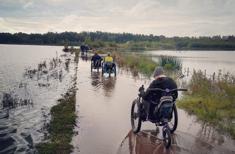 Group of disabled people in all-terrain wheelchairs going through a wet and boggy path