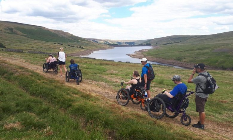 Group of disabled people in all-terrain wheelchairs next to Scar House Reservoir