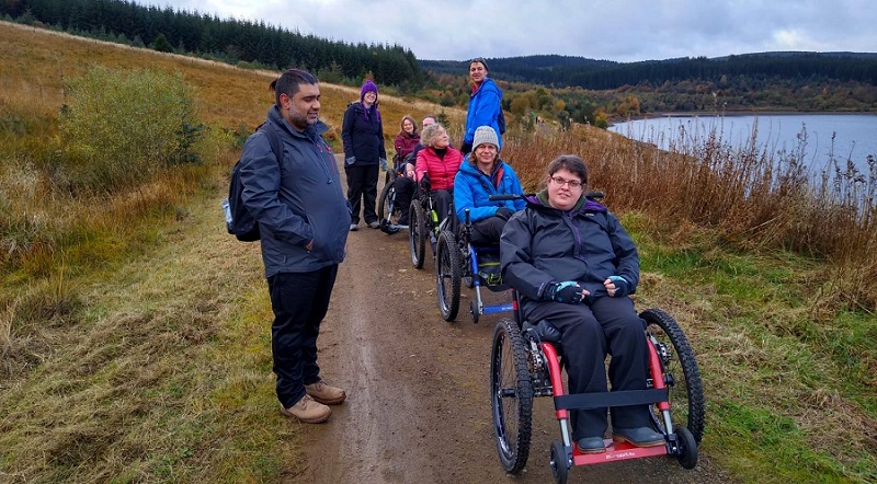 Group of disabled people in all-terrain wheelchairs on a ramble next to a lake