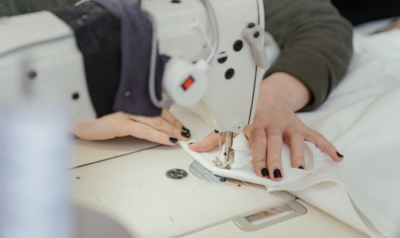 Hands putting white cloth through a sewing machine