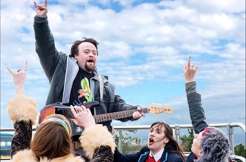 James Martin holding a guitar with his arm in the air at a music festival in the film Ups and Downs