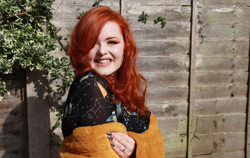 Lucy Edwards in front of a wooden fence with red hair wearing a black dress and yellow cardigan