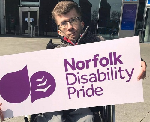 Man in a wheelchair holding the Norfolk Disability Pride sign